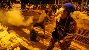 An anti-government protester throws a tear gas canister towards police during clashes near the Government House in Bangkok.