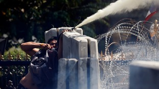 An anti-government protester sprays an unknown substance over the barricade during clashes with police.