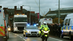 Police officers line the street as the wreckage of the police helicopter is taken away by lorry
