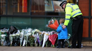 A police officer escorts a child laying flowers for the victims of the Glasgow helicopter crash