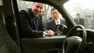 Prime Minister David Cameron looks at a black cab with Geely Chairman Li Shufu.
