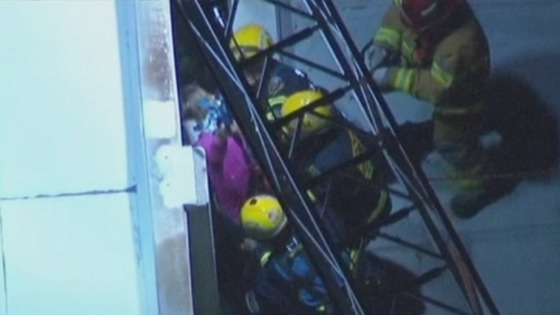 A 28-year-old woman being rescued from the gap between two buildings in California last night.