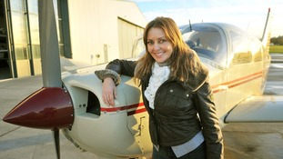 Carol Vorderman leaning on a plane at the Staverton Flying School at Gloucester Airport.