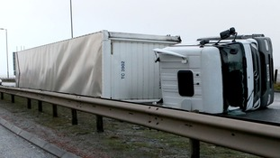 A lorry sits on its side after been blown over in high winds on the A725 near Hamilton
