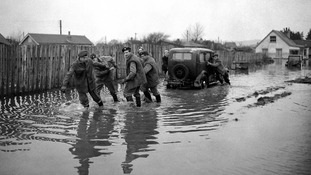 Servicemen hauling a car through the flood water at Canvey Island, Essex