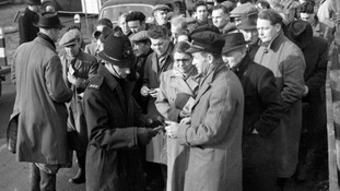 A policeman checking people's ration cards and other documents at the entrance to Canvey Island