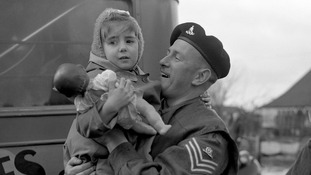 A Royal Artillery sergeant carries a small evacuee