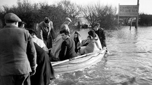 Wrapped in blankets, children and adults are ferried by boat through the flood waters at Jaywick, near Clacton, Essex