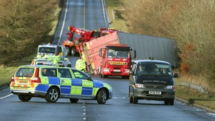 Police and recovery vehicles at the scene where a lorry driver has died as his HGV toppled on to a number of cars on the A801.