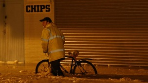 A man pushes his bike through flood water in Great Yarmouth in Norfolk