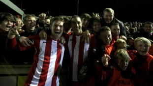 Brackley's players celebrate with fans after beating Gillingham.