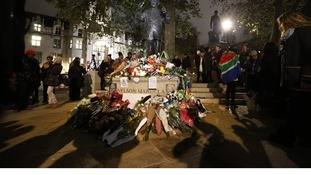People gather around a statue of  Nelson Mandela at Parliament Square.