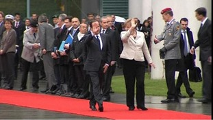 Hollande and Merkel walk the red carpet in Berlin