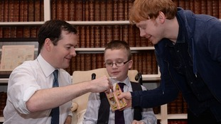 Chancellor George Osborne meets actor Rupert Grint share some Christmas cookies with 9-year-old Callum Wilson.