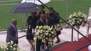 Winnie Mandela can be seen carrying the black umbrella