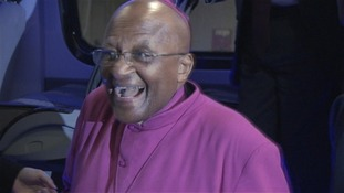 Archbishop Desmond Tutu smiles as he arrives at the stadium in Johannesburg