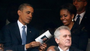 President Obama looks through a programme with his wife Michelle