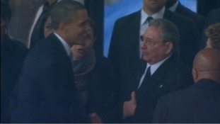 Obama shakes the hand of Castro.