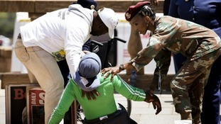 Soldiers help a woman as she collapses after seeing Nelson Mandela's coffin.