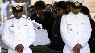 Nelson Mandela's ex-wife Winnie pays her respects at his coffin.