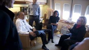 Former Secretary of State Hillary Clinton talks with the Obamas en route to South Africa.