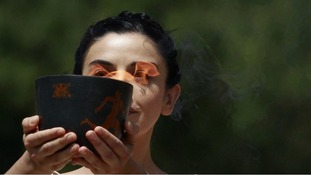 Actress playing High Priestess carries cauldron carrying Olympic Flame during torch lighting ceremony in Greece