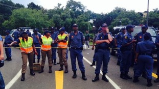 Police line the street in Pretoria where a crowd has gathered.