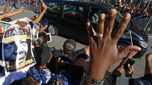 People react as the hearse carrying Nelson Mandela travels through a street in Pretoria.