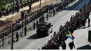 Mourners line along the street as the funeral cortege drives to the Union Buildings in Pretoria.