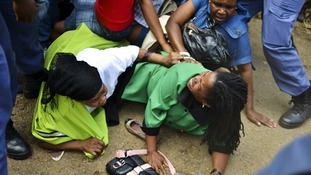 Mourners fall in a stampede as they run to queue before boarding buses to take them to the Union Buildings
