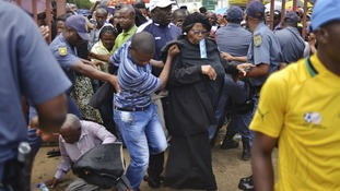 A man falls to the ground as mourners push through the metal gates in Pretoria.
