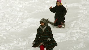 Children making the most of the snow in Amman