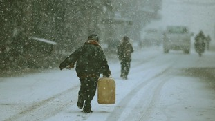 A Damascus resident struggles through slippery streets
