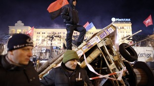 Protesters stand guard at a barricade at Independence Square in Kiev.