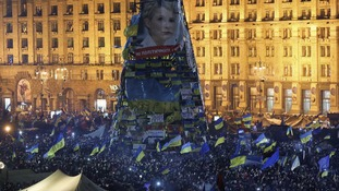 Protesters gather under an image of jailed opposition leader Yulia Tymoshenko.