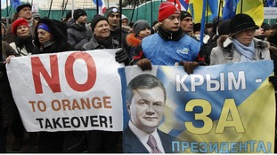 Supporters of Ukranian President President Viktor Yanukovich hold flags and placards during a rally in central Kiev.