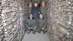 Kim Jong-un poses for pictures among the frozen squid.