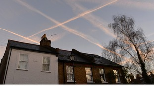 Contrails from passenger planes seen at dawn near Heathrow Airport in west London.