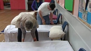 Volunteers prepare the beds at the shelter.