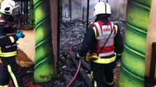 Firefighters access the damage by this morning's blaze.