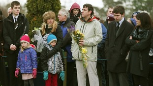 Relatives prepare to lay flowers during the memorial service