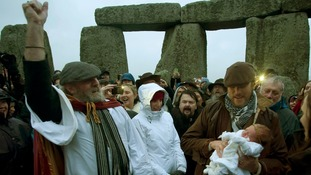 Archdruid of Stonehenge Rollo Maughfling (left) blesses four month-old baby Jim held by father Dan