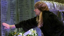 A woman touches the wall of remembrance at Dryfesdale Cemetery in Lockerbie