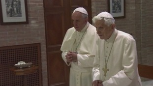Pope Francis and Benedict XVI pray together in a chapel adjoining the former pontiff's residence.