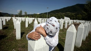 Adila Suljakovic cries at the grave of her son in the Memorial Center in Potocari, near Srebrenica.
