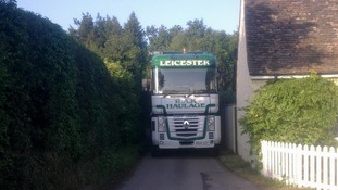 A lorry struggles to get through a village road