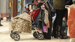 A baby is all but lost in the pile of cut-price clothes at Highcross in Leicester