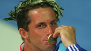 Ben Ainslie kisses his gold medal after the win in the Finn dinghy class in the Athens 2004