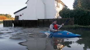 A man paddles his canoe past a flooded property in Yalding on Boxing Day