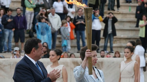 The Princess Royal is presented with the torch during the official handover ceremony at the Panathenaic Stadium.